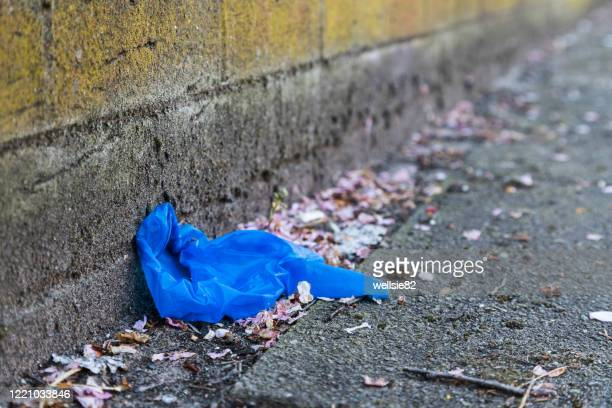 discarded blue ppe - surgical glove stock pictures, royalty-free photos & images