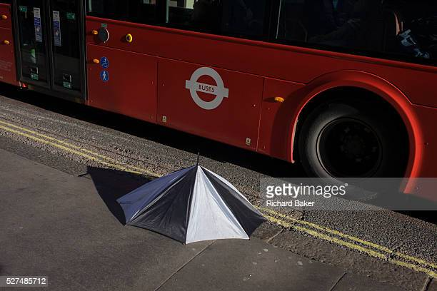 A discarded broken umbrella and side of a bus in Charing Cross Road central London The broken brolly sits upright on the pavement as daily life in...