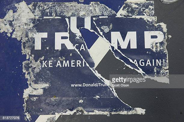 Discarded campaign posters are stuck to the floor following a rally with Republican presidential candidate Donald Trump at Macomb Community College...