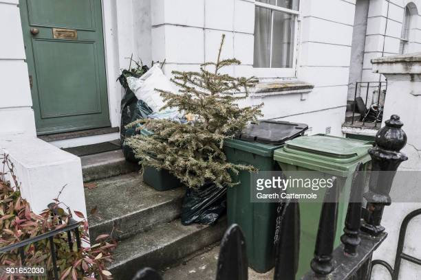 A discarded Christmas tree stands amongst rubbish in Angel on January 5 2018 in London England In the lead up to Christmas a pine tree is the centre...