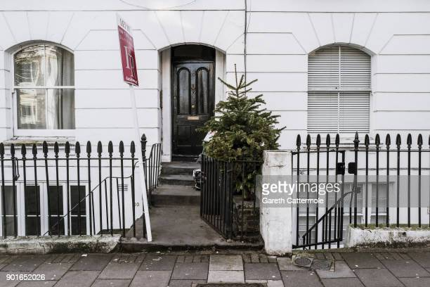 A discarded Christmas tree stands amongst rubbish outside a house in Angel on January 5 2018 in London England In the lead up to Christmas a pine...