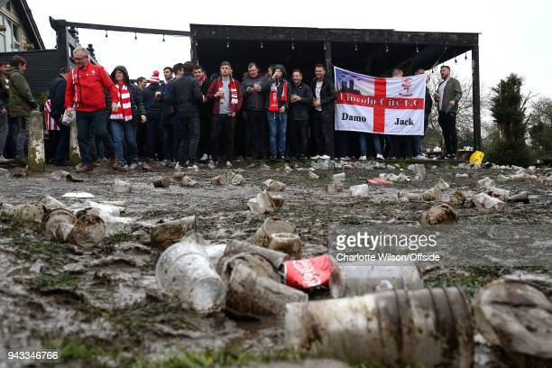 Discarded cups and cans are left out in the rain and mud as Lincoln fans shelter in a covered bar area ahead of the Checkatrade Trophy Final between...