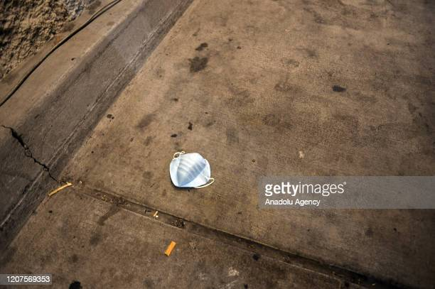 Discarded face mask lies on the sidewalk outside a Safeway in San Jose on March 18, 2020.