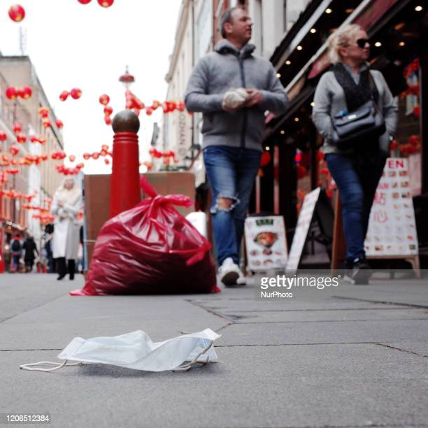 Discarded face mask, worn as a precaution against transmission of the covid-19 coronavirus, lies on Gerrard Street in Chinatown in London, England,...