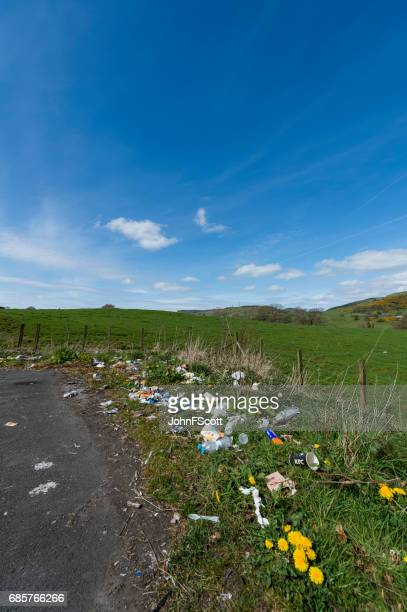 discarded litter at the side of a rural road in scotland - johnfscott stock pictures, royalty-free photos & images