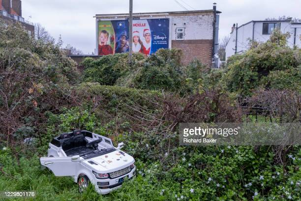 Discarded miniature child's toy car and nearby billboards ads promoting Disney Christmas films, in East Dulwich, on 25th December 2020, in London,...