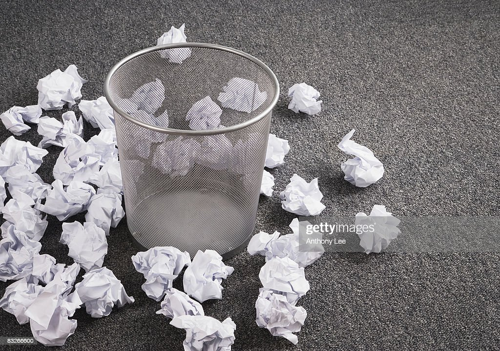 Discarded paper on floor around wastebasket : Stock Photo