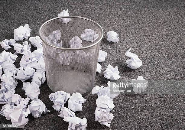 Discarded paper on floor around wastebasket