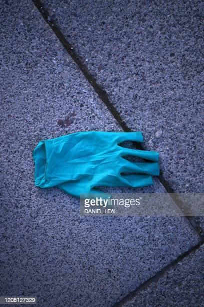 Discarded plastic glove is pictured in London on the morning on March 24, 2020 after Britain ordered a lockdown to slow the spread of the novel...