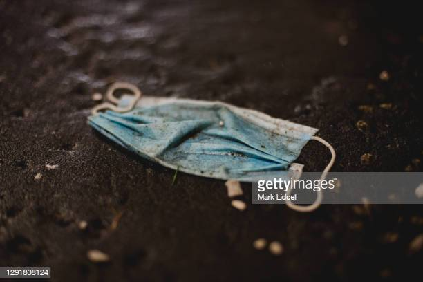 discarded ppe surgical mask littering the street - plastic pollution - protective face mask stock pictures, royalty-free photos & images