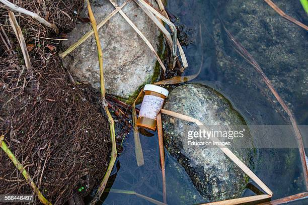 A discarded prescription bottle in the Los Angeles River after the first rain of the season Glendale Narrows Los Angeles California