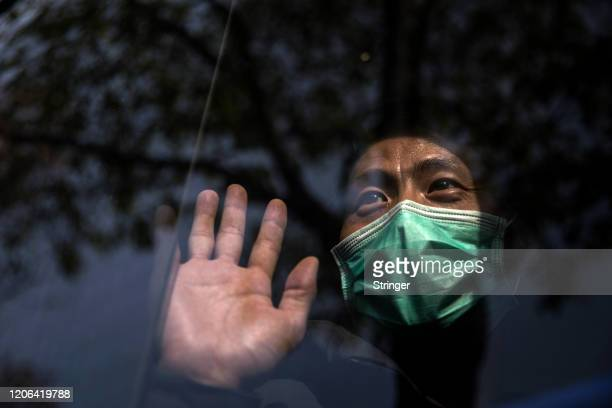 A discharged COVID19 patient waves from the bus while departing Wuchang Fang Cang makeshift hospital which is the latest temporary hospital being...