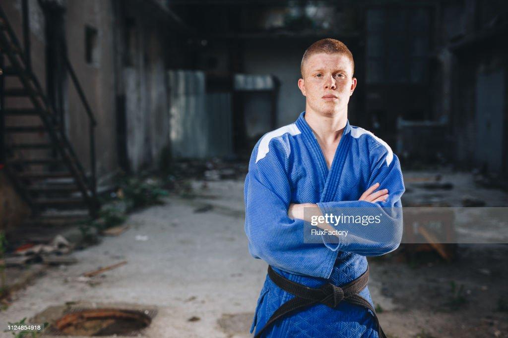 Disciplined judo practitioner in a blue kimono : Stock Photo