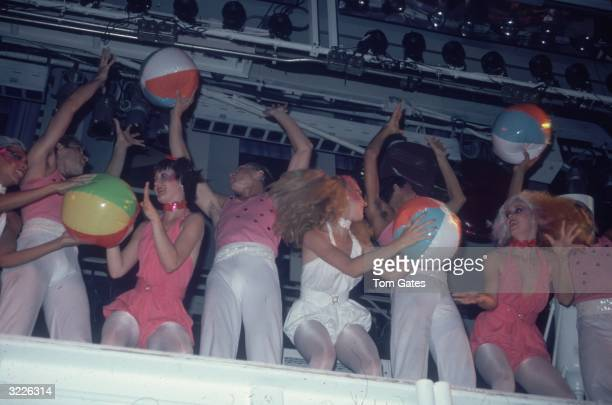 Disco dancers in matching pink and white costumes play with beach balls on the mezzanine of Studio 54 a nightclub in New York City The line of...