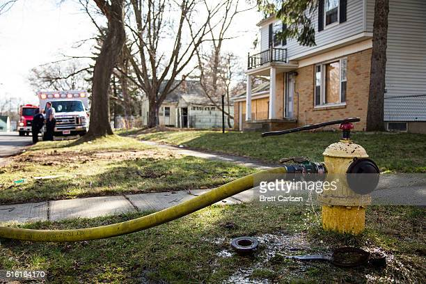 Discolored water leaks from a fire hydrant as Flint Fire Department works to put out a fire in an abandoned home on March 17 2016 in Flint Michigan...