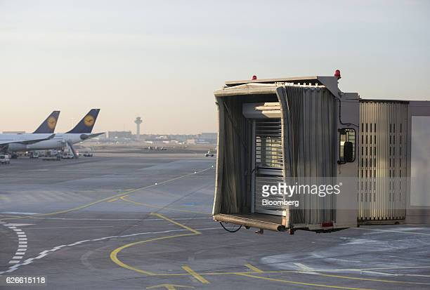 A disconnected passenger walkway stands as Frankfurt Airport as a pair of Deutsche Lufthansa AG passenger jets sit beyond as the German airline's...