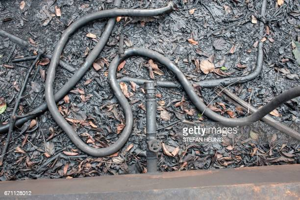 A disconnected pipe lies on the ground at the outlet of an illegal oil refinery storage tank on April 19 2017 in the Niger Delta region near the city...