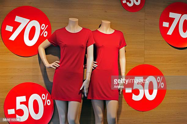 Discount notices showing deductions in shop window of clothes store during the summer sales in shopping street