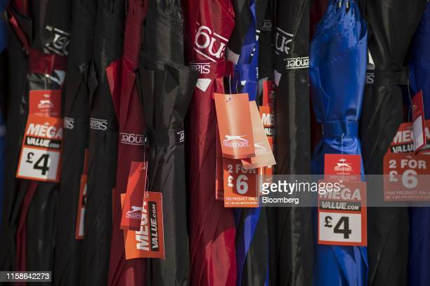 Discounted umbrellas sit on display outside a Sports Direct International Plc store in Crayford UK on Monday July 29 2019 Sports Direct plunged after...