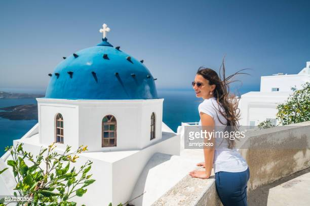 discovering greece - woman on santorini island with blue and white greek church - chapel stock pictures, royalty-free photos & images