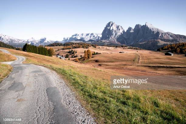Discovering the beautiful Dolomites mountains with meadows and alpine houses in Alpe di Siusi.