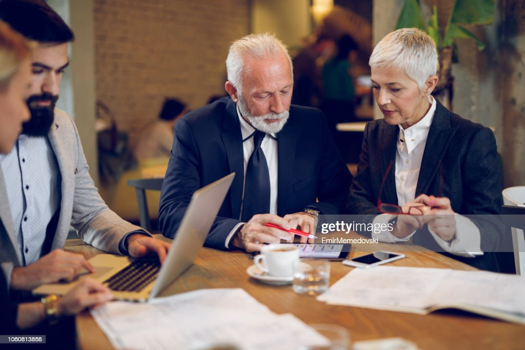 Discussing business decisions in a meeting in cafe : Stock Photo