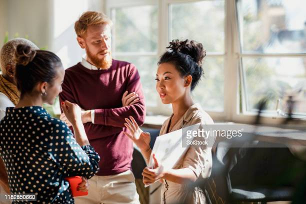discussing business with colleagues - multi ethnic group stock pictures, royalty-free photos & images