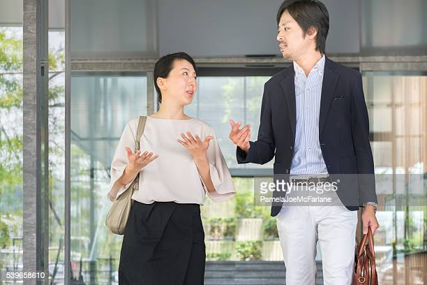 Discussion Between Japanese Businesswoman and Businessman Leaving Office Lobby Entrance