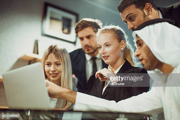 Discussion on a laptop between multicultural business professional