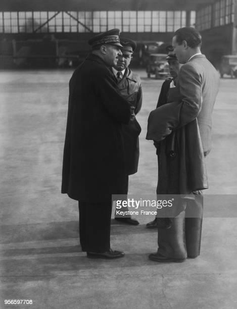 Discutant ensemble avant le départ, le ministre de l'Air le général Denain avec Messieurs Rossi, Mermoz et le capitaine Girardot, à Villacoublay,...