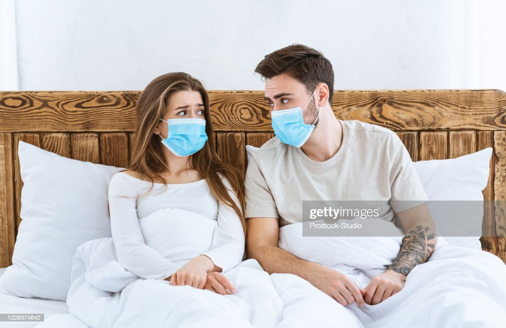 Disease and quarantine concept. Sad guy and girl in protective masks are sitting in bed : Stock Photo
