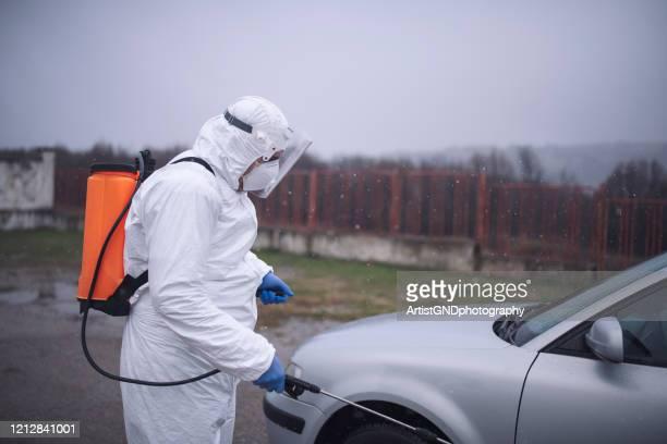 seuchenbekämpfungservice personal desinfizieren auto zur verhinderung der verbreitung covid-19 - landfahrzeug stock-fotos und bilder