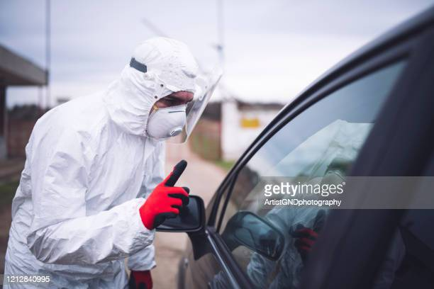 disease control service staff standing in front of geographic border  and sign with hand on car driver. - centers for disease control and prevention stock pictures, royalty-free photos & images