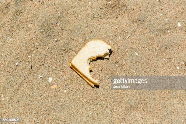 Disgraced half eaten sandwich on beach