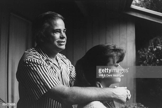 Disgraced PTL evangelist Jim Bakker outside resting his arms on his daughter Tammy Sue's shoulders on the Bakker family's first day in their new house