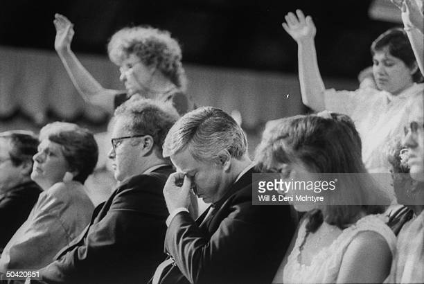 Disgraced PTL evangelist Jim Bakker praying in audience of PTL Camp Meeting show daughter Tammy Sue and her husband Doug Chapman and lawyer Jim Toms...