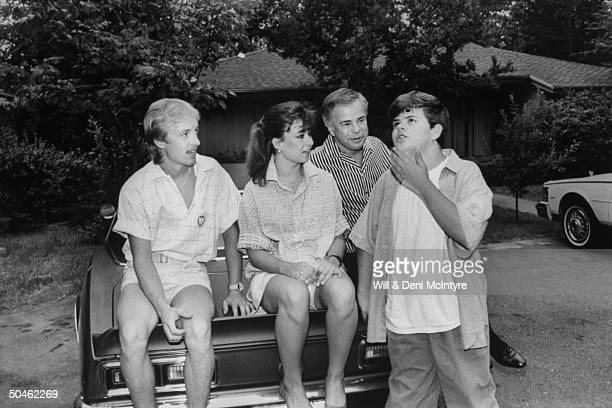 Disgraced televangelist James Bakker w his soninlaw Doug Chapman his son Jamie daughter Tammy Sue sitting on car in front of home after returning...