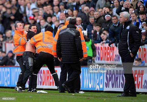 A disgruntled Newcastle fan shouts at Alan Pardew the Newcastle manager as he is removed from the pitch by stewards during the Barclays Premier...