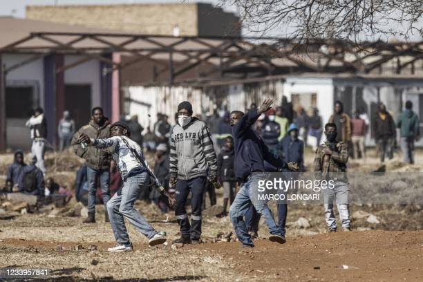 Disgruntled residents throw rocks as they confront police officers at the entrance of a partially looted mall in Vosloorus, on July 13, 2021. -...