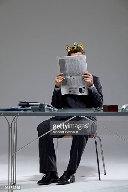 CEO disguised as a king reading newspaper