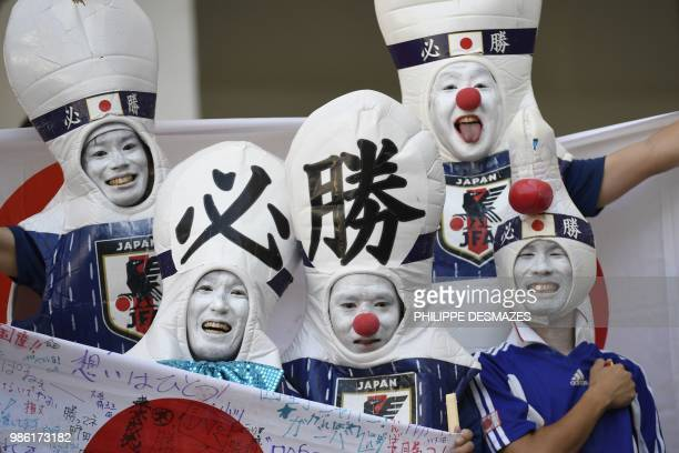 Disguised Japan's fans cheer their team before the Russia 2018 World Cup Group H football match between Japan and Poland at the Volgograd Arena in...