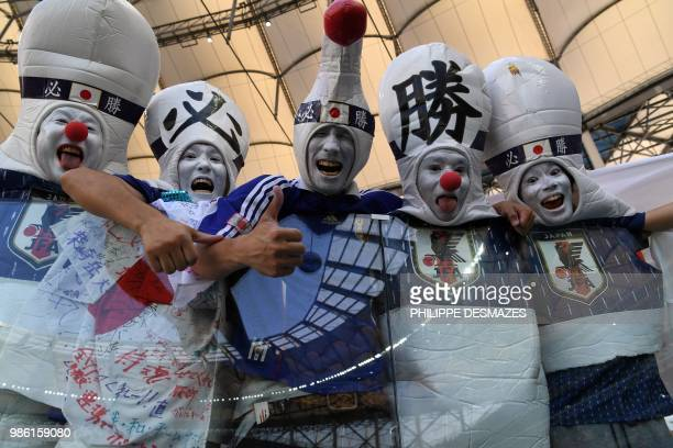 TOPSHOT Disguised Japan's fans gesture as they pose before the Russia 2018 World Cup Group H football match between Japan and Poland at the Volgograd...