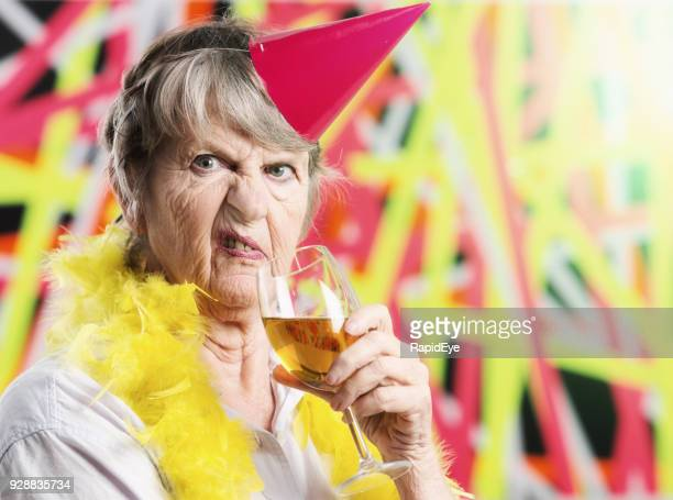 Disgusted old woman in party hat does not approve