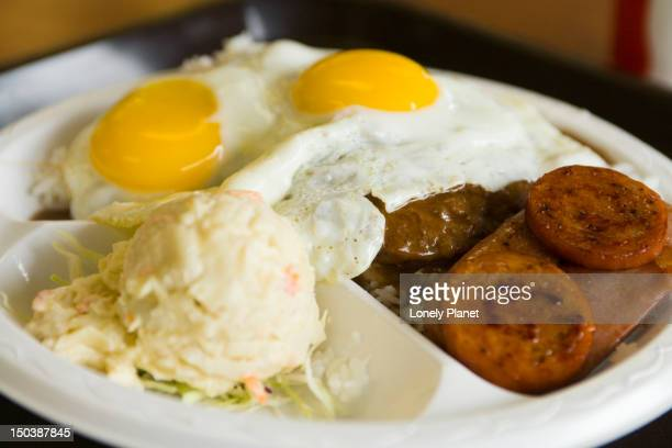 disgusting to some, a loco moco (burger, rice, egg, gravy) also with spam, tomato and macaroni salad, at cafe 100, hilo, east coast. - plastic plate stock photos and pictures
