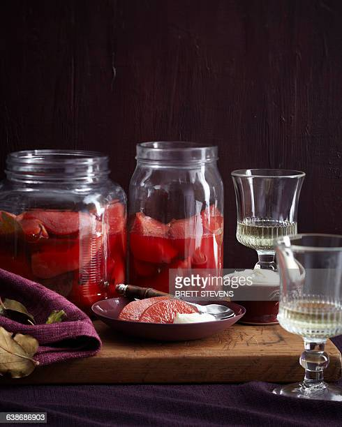 Dish and jars of homemade poached quince on cutting board