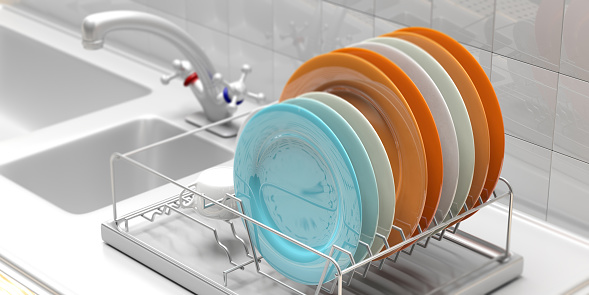 Dish drying rack with colorful plates on a white kitchen counter. 3d illustration 1036926476