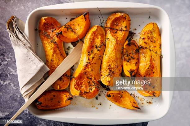 dish of baked butternut squashes ready to eat. - roasted stock pictures, royalty-free photos & images