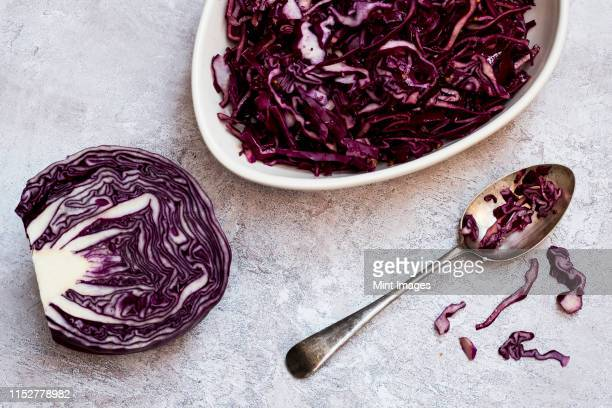a dish of cooked red cabbage and half a raw cabbage. - rodekool stockfoto's en -beelden