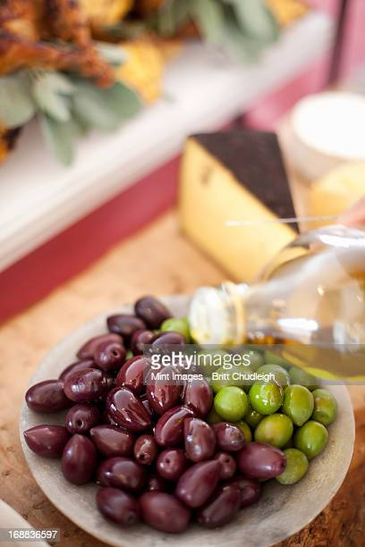 a dish of fresh organic vegetables. green and black olives on a plate with a drizzling of olive oil from a bottle. prepared farmstand foods for a party - bottle green stock pictures, royalty-free photos & images