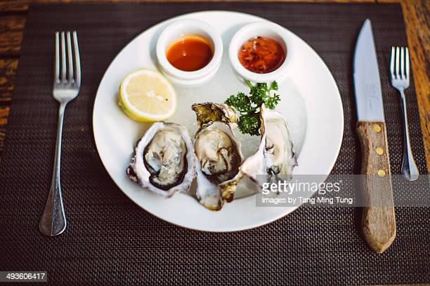 A dish of fresh oysters on dining table